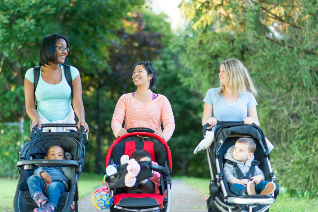 Mums with babies in pushchairs walking in park