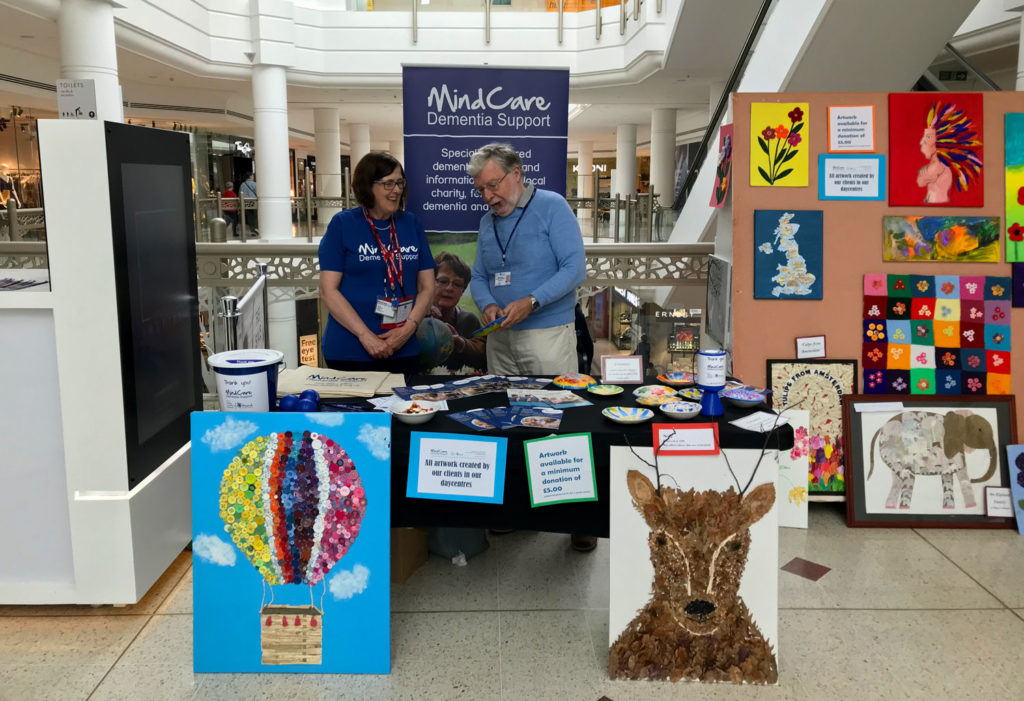 Two volunteers at shopping centre at a charity stall