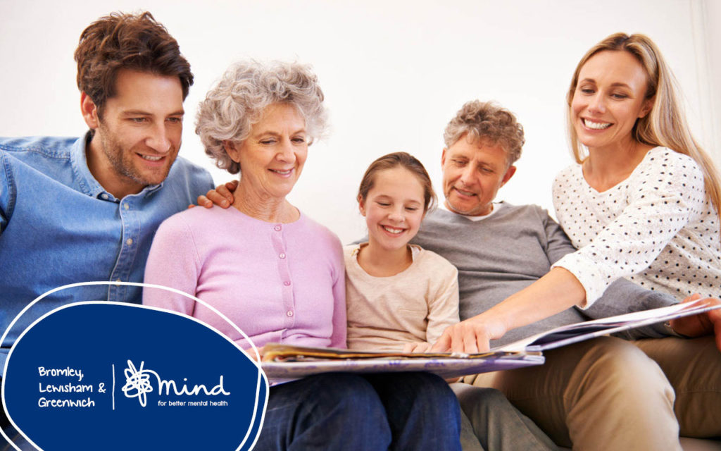 a multi-generational family looking at a photo album