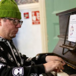 Man with a green woolly hat playing the piano at Bromley World Mental Health Day 2019 event